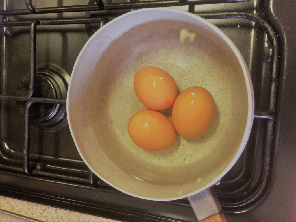 Three eggs in a saucepan waiting to be boiled