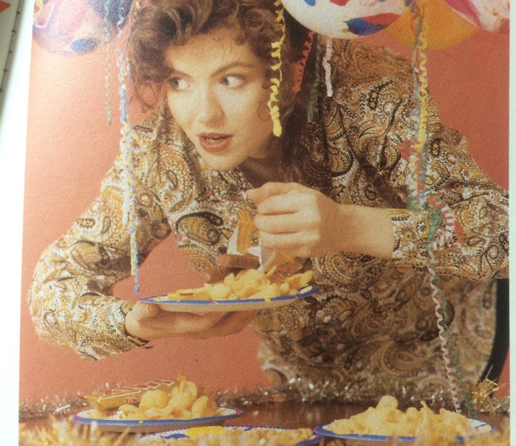 Nineties photo of teenage girl eating crisps at a party.