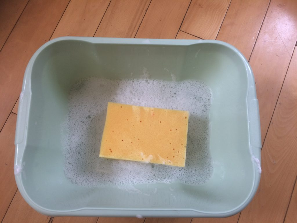 A sponge and soapy water in a basin