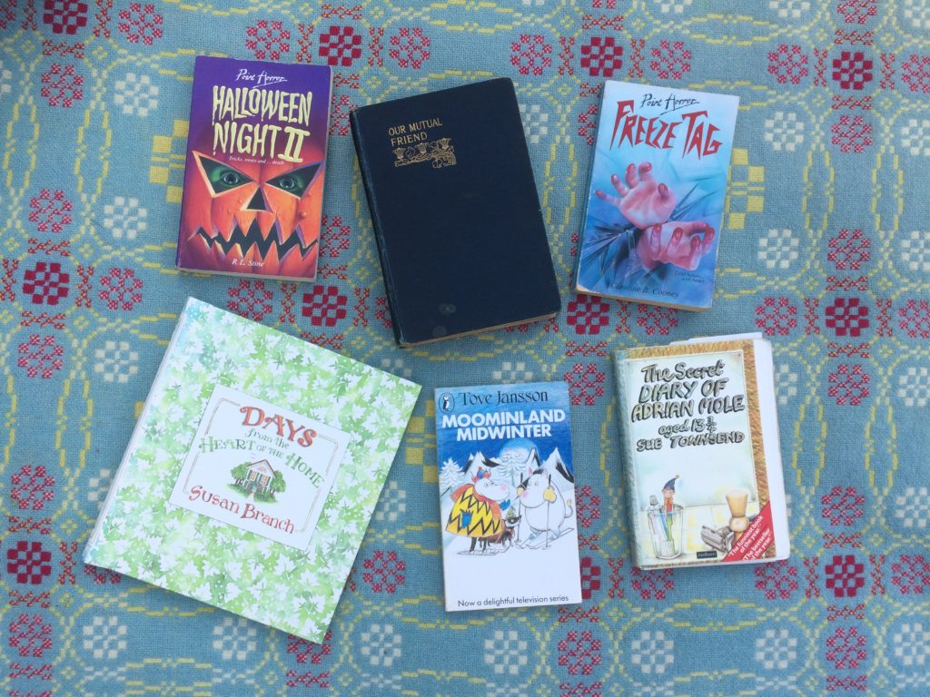 Six books, one by R.L. Stine, one by Charles Dickens, one by Caroline B. Cooney, one by Susan Branch, one by Tove Jansson, one by Sue Townsend.