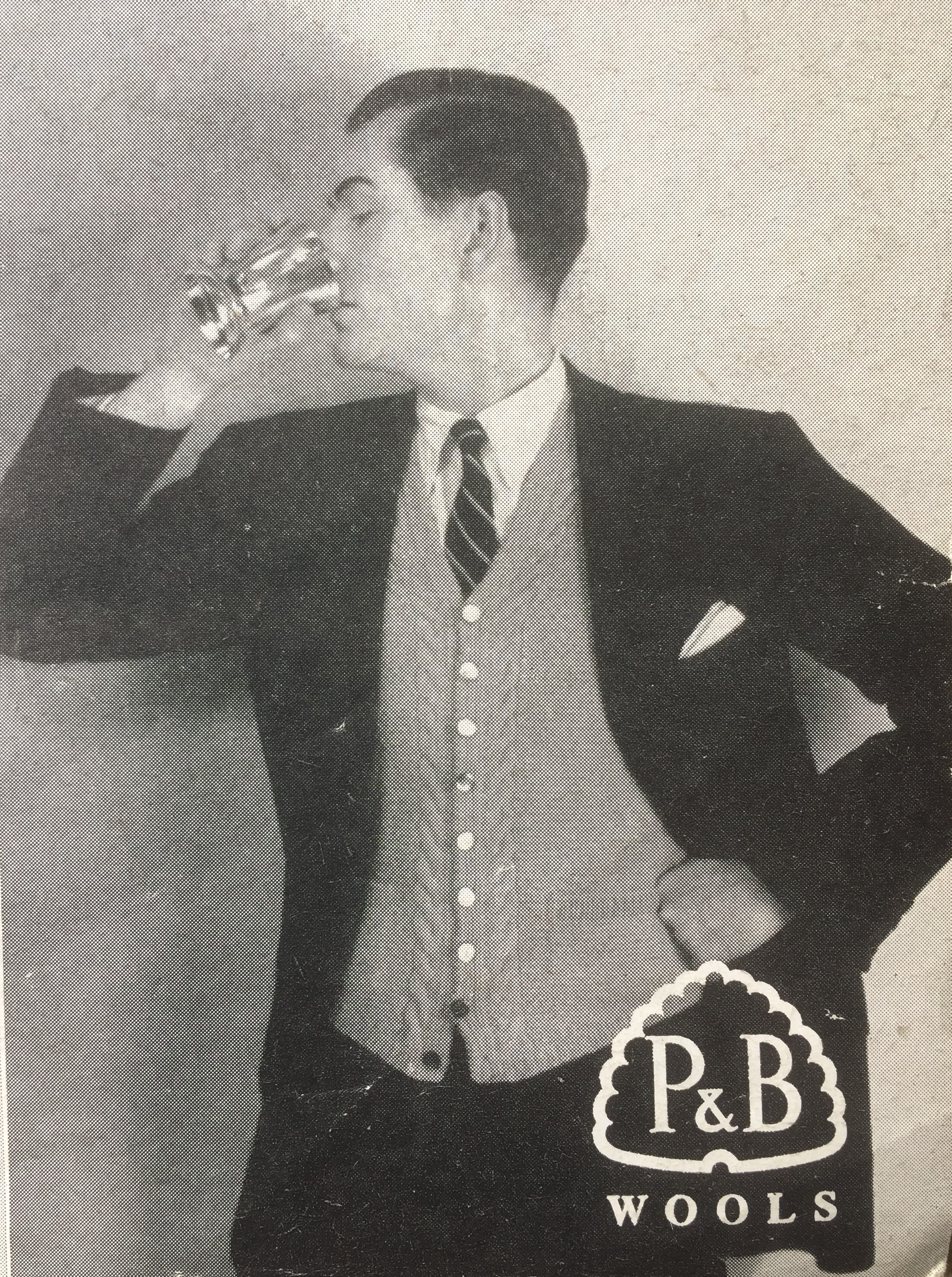 Vintage photo of male sweater model drinking a glass of something alcoholic perhaps