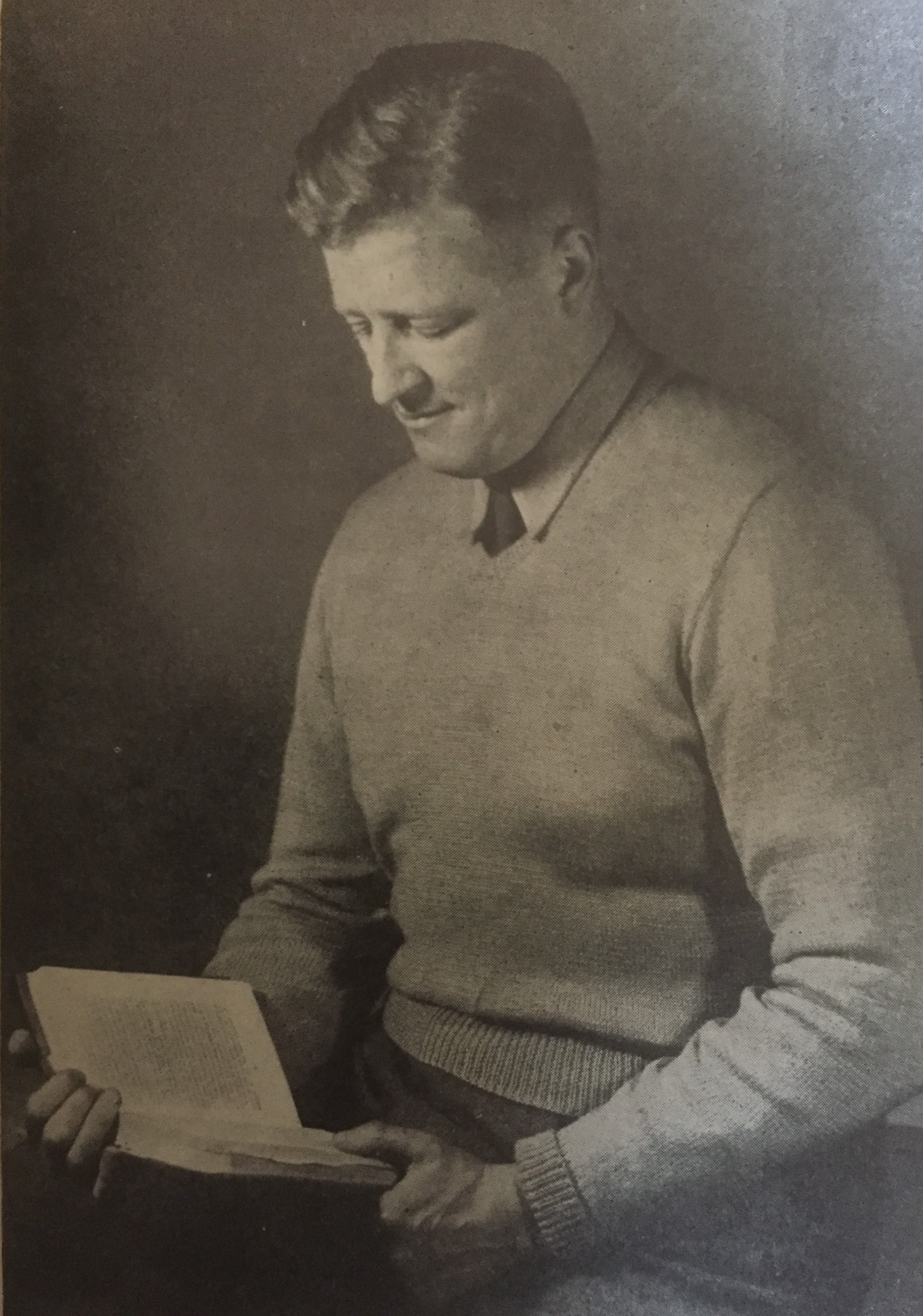 Vintage photo of man in v neck jumper reading a book