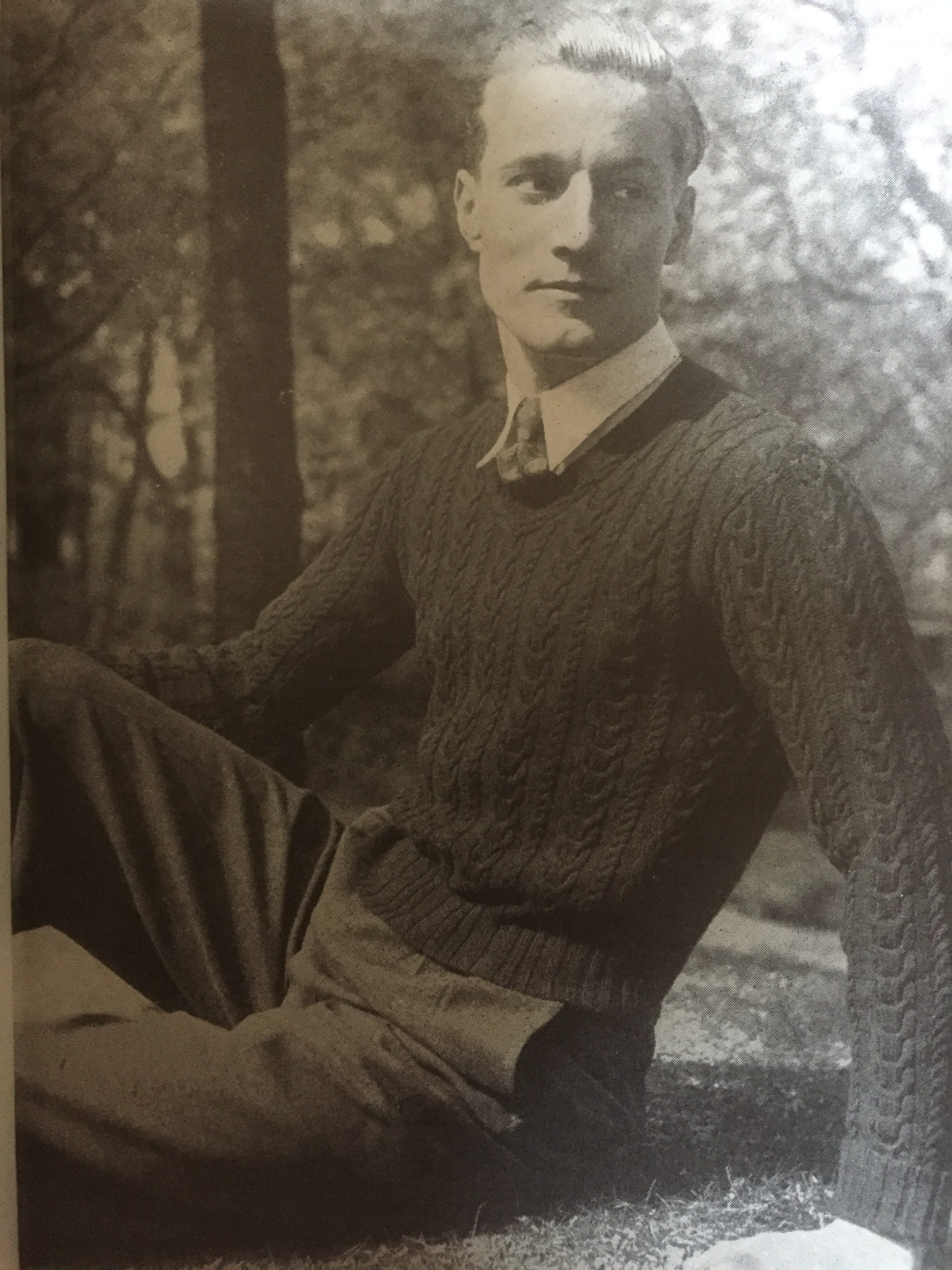 vintage photo of male knitwear model leaning on the ground in a park