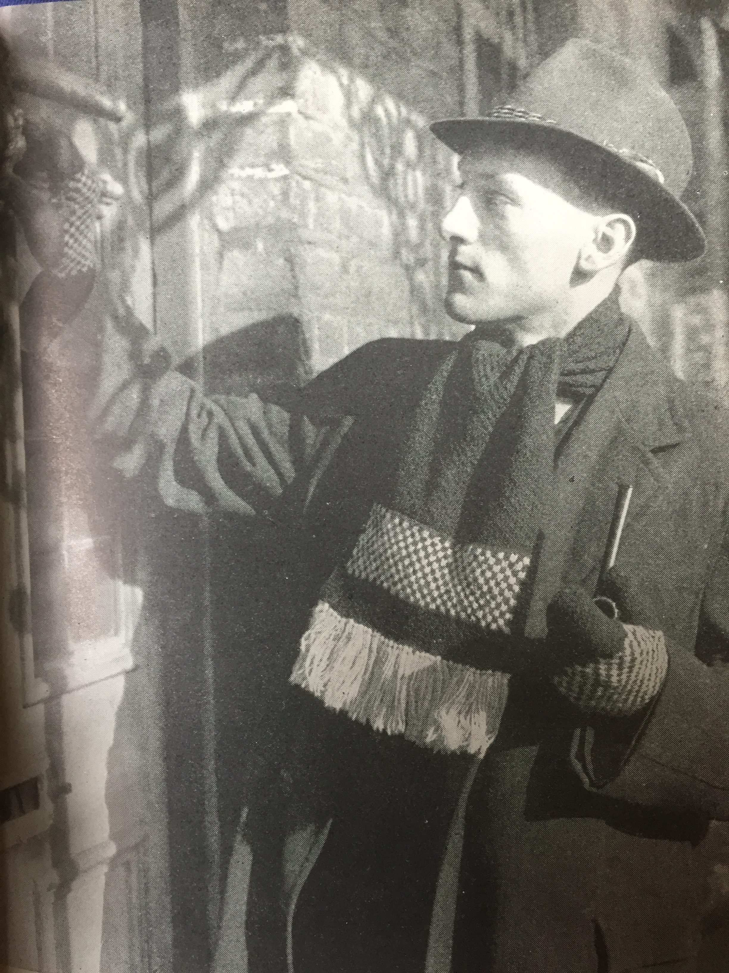 vintage photo of male knitwear model knocking on door with pipe in hand